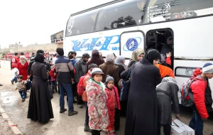 Women and children board buses to leave the al-Waer neighbourhood bound for a town on the Turkish border, in Homs, Syria, Saturday, March 18, 2017. (AP)