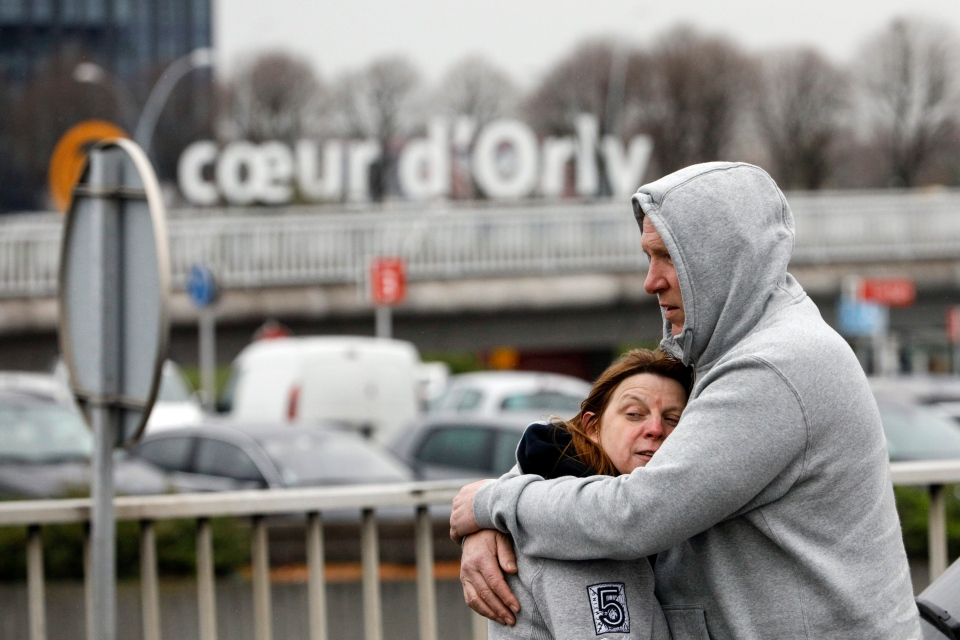 Travellers hug outside Orly airport, south of Paris, Saturday, March, 18, 2017. (AP Photo/Kamil Zihnioglu)