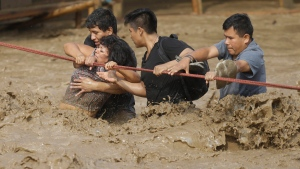 A group of people, stranded in flood waters, hold onto a rope as they wade through flood waters to safety in Lima, Peru, Friday, March 17, 2017. (AP Photo/Martin Mejia)