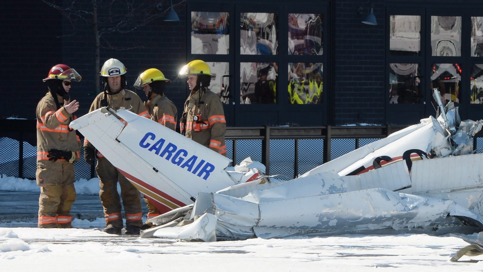 Firefighters look at the wreckage from a plane crash as it sits in a parking lot in Saint-Bruno, Que., on Friday, March 17, 2017. (Ryan Remiorz/THE CANADIAN PRESS)