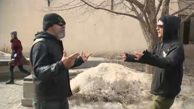 A protester wearing a Soldiers of Odin Canada jacket (left) argues with protesters from a counter rally.