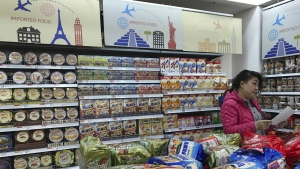 A vendor takes stock of imported food at a mall in Beijing, China on Friday, March 17, 2017. (AP / Ng Han Guan)