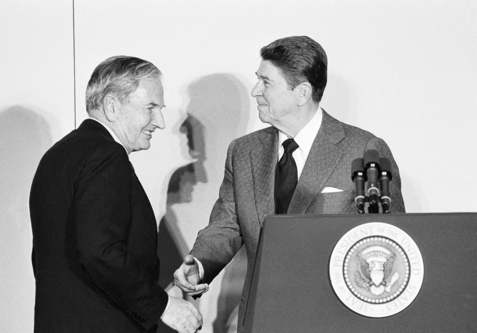 In this May 8, 1984 file photo, David Rockefeller, left, chairman of the Council Americas, shakes hands with President Ronald Reagan at the State Department in Washington. (AP Photo/Ira Schwarz, File)