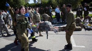 In this Tuesday, March 1, 2016 file photo, American servicemen and Israeli soldiers participate in a joint drill simulating a rocket attack at a base in Hatzor, central Israel. Israel is making contingency plans to evacuate up to a quarter million people from communities along the Gaza and Lebanese borders to get them away from missile attacks if war erupts again with Hamas or Hezbollah. (AP Photo/Sebastian Scheiner, File)