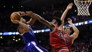 Toronto Raptors guard DeMar DeRozan drives to the net to set up teammate Toronto Raptors forward Patrick Patterson as Chicago Bulls forward Jimmy Butler and Chicago Bulls forward Paul Zipser defend during overtime NBA basketball action, in Toronto on Tuesday, March 21, 2017. (Frank Gunn / THE CANADIAN PRESS)