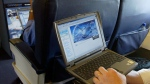 A laptop is being used on a plane. (Chris Ison / PA, via AP)