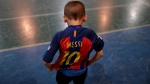 Benjamin Palandella puts on his Barcelona jersey adorned with Messi's number 10 at Club Social Parque, on Nov. 11, 2016. (Natacha Pisarenko / AP)