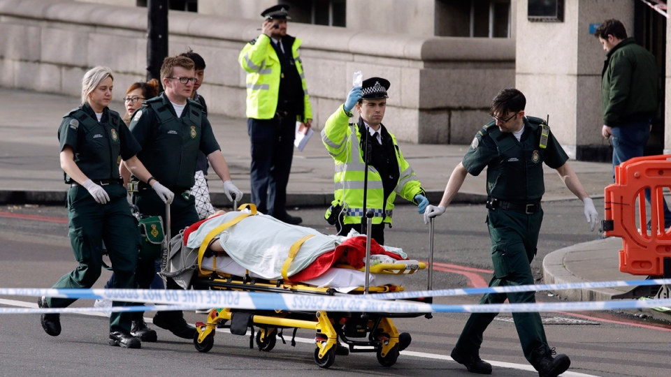 Emergency services staff provide medical attention close to the Houses of Parliament in London, on March 22, 2017. (Matt Dunham / AP)