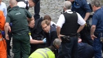 Conservative Member of Parliament Tobias Ellwood, centre, helps emergency services attend to an injured person outside the Houses of Parliament, London, Wednesday, March 22, 2017.  (Stefan Rousseau/PA via AP).
