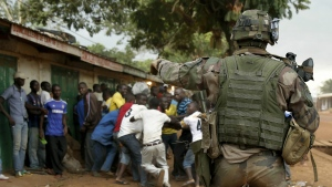 A French soldier screams at mobs of Christians attacking suspected Seleka members before firing warning shots near the airport in Bangui, Central African Republic on Dec. 9, 2013. (AP / Jerome Delay)