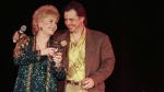In this April 1, 1997, file photo, Debbie Reynolds, left, celebrates her 65th birthday on stage as her son, Todd Fisher, presents her with a cake following her evening variety show, at the Debbie Reynolds Hotel in Las Vegas. (AP Photo/Lennox McLendon, File)