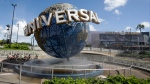 FILE - In this Thursday, Oct. 22, 2015 file photo, park guests relax and cool off with a water mist under the globe at Universal Studios City Walk in Orlando, Fla. (AP Photo/John Raoux)