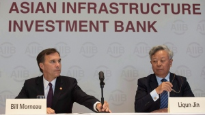Canadian Minister of Finance Bill Morneau adjusts a microphone as he sits with the President of the Asian Infrastructure Investment Bank Jin Liqun during a news conference at the Asian Infrastructure Investment Bank in Beijing, August 31, 2016. (Adrian Wyld / The Canadian Press)