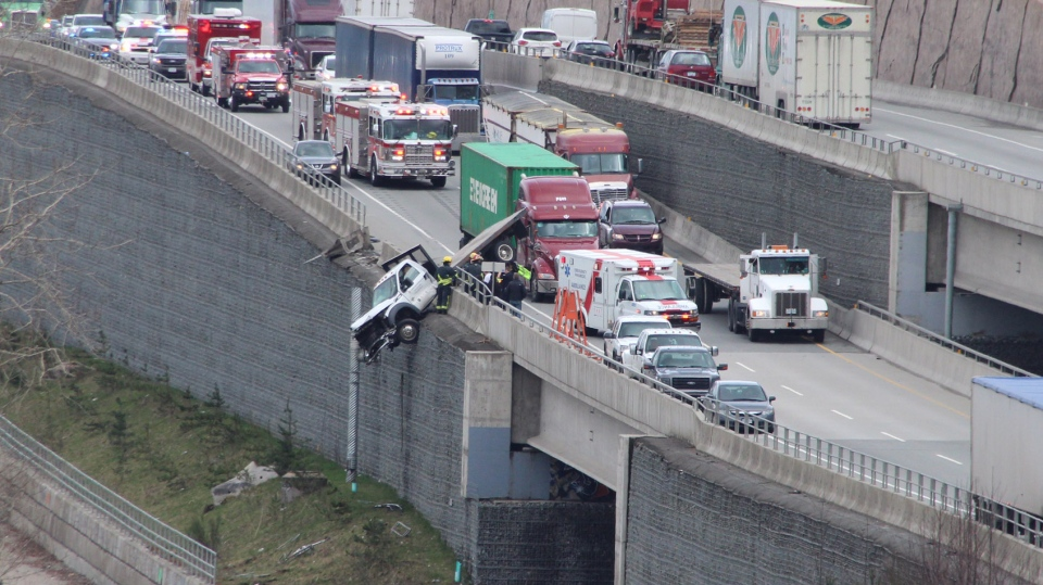 The truck plowed through the concrete barrier and was left with its rear tires off the ground. (CTV)