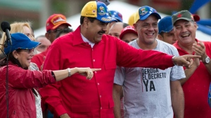 First lady Cilia Flores, left, Venezuela's President Nicolas Maduro, second left and Caracas Mayor's Jorge Rodriguez, second right smile during an anti-imperialist rally in Caracas, Venezuela, Thursday, March 9, 2017. (AP Photo/Ariana Cubillos)