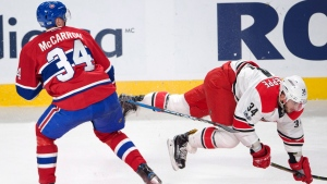 Carolina Hurricanes left wing Phillip Di Giuseppe is upended by Montreal Canadiens right wing Michael McCarron (34) during second period NHL hockey action, in Montreal on Thursday, March 23, 2017. (Ryan Remiorz / THE CANADIAN PRESS)
