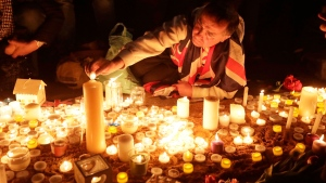People light candles at a vigil for the victims of Wednesday's attack, at Trafalgar Square in London, Thursday, March 23, 2017. (AP Photo/Matt Dunham)