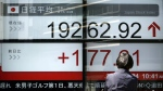 A woman looks at an electronic stock board showing Japan's Nikkei 225 index at a securities firm in Tokyo on Friday, March 24, 2017. (AP / Eugene Hoshiko)