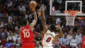 Toronto Raptors guard DeMar DeRozan shoots under pressure from Luke Babbitt and Josh Richardson of the Miami Heat in the first quarter of an NBA basketball game in Miami on Tuesday, March 23, 2017. (AP / Joe Skipper)