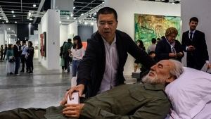 In this picture taken on March 22, 2017, Chinese artist Shen Shaomin places his phone in the hands of a replica of Fidel Castro, part of his 'Summit' project, at Art Basel in Hong Kong. (Anthony Wallace/AFP)