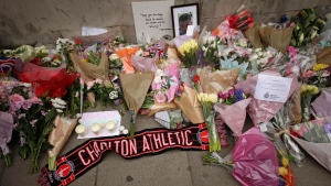Tributes to victims of Wednesday's attack laid outside the Houses of Parliament in London, Friday March 24, 2017. On Thursday authorities identified a 52-year-old Briton as the man who mowed down pedestrians and stabbed a policeman to death outside Parliament in London, saying he had a long criminal record and once was investigated for extremism — but was not currently on a terrorism watch list. (AP Photo/Matt Dunham)