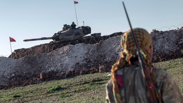 In this February 22, 2015, file photo, a Syrian Kurdish militia member of the YPG patrols near a Turkish army tank as Turks work to build a new Ottoman tomb in the background in Esme village in Aleppo province, Syria. (AP Photo/Mursel Coban, Depo Photos, File)