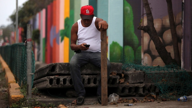 FILE -- A man checks his cell phone as he stands guard in a commercial zone in the port city of Veracruz, Mexico, Friday, Jan. 6, 2017. (AP Photo/Felix Marquez)