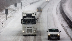 Cars make their way through snowfall on highway 19 between Berlin and Rostock, near Linstow, Germany, Wednesday Jan 11, 2017. (Bernd Wuestneck/dpa via AP)