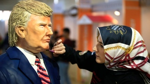Turkish pastry chef Tuba Geckil adds the finishing touches to her figure of US President Donald Trump made out of cake icing which she created in two days, during a chocolate show in Istanbul, Saturday, March 25, 2017. (AP Photo/Lefteris Pitarakis)