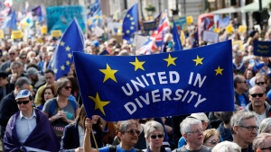 Anti Brexit campaigners carry flags and banners as they march towards Britain's parliament in London, Saturday March 25, 2017. Britain's Prime Minister Theresa May is expected to start the process of leaving the European Union on Wednesday March 29. (AP Photo/Kirsty Wigglesworth)