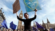 Anti Brexit campaigners carry flags and banners outside Britain's parliament in London, Saturday March 25, 2017. Britain's Prime Minister Theresa May is expected to start the process of leaving the European Union on Wednesday March 29. (AP Photo/Kirsty Wigglesworth)