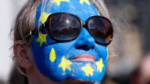 A woman with her face painted in the colours of the European flag stands with other anti Brexit campaigners outside Britain's parliament in London, Saturday March 25, 2017.  (AP /Kirsty Wigglesworth)