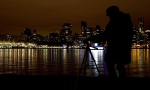 In this file photo, a woman takes photographs along the Stanley Park seawall after many downtown buildings turned their lights off during Earth Hour in Vancouver, B.C., on Saturday March 31, 2012. (Darryl Dyck / THE CANADIAN PRESS)