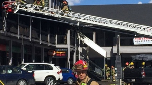 Calgary Fire Department members survey the damage to the Urban Square strip mall