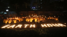 Activists light candles and hold torches as buildings turn their exterior lights off during the Earth Hour at the main business district in Jakarta, Indonesia, Saturday, March 25, 2017. Earth Hour takes place worldwide and is a global call to turn off lights for 60 minutes in a bid to highlight the global climate change. (Tatan Syuflana / AP)