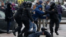 A woman, pushed to the ground by Belarus police, tries to defends herself as the police detain an activist during an opposition rally in Minsk, Belarus, Saturday, March 25, 2017. (AP Photo/Sergei Grits)