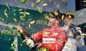 Ferrari driver Sebastian Vettel of Germany sprays champagne as confetti falls around him after winning the Australian Formula One Grand Prix in Melbourne, Australia, Sunday, March 26, 2017. At right is Mercedes driver Valtteri Bottas who finished third. (AP / Andy Brownbill)
