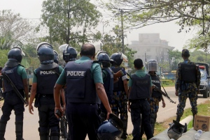 Bangladeshi policemen watch as paramilitary soldiers try to flush out Islamist radicals who have holed up in a building with a large cache of ammunition in the city of Sylhet, Bangladesh, Sunday, March 26, 2017. (AP / A. H. Arif)
