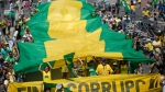 People hold a gaint flag with the national colors of Brazil during a protest against corruption at Copacabana beach, in Rio de Janeiro, Brazil, Sunday, March 26, 2017. (AP Photo/Silvia Izquierdo)
