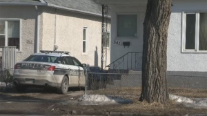 A Winnipeg police vehicle parked in front of the Burrows Avenue home on Sunday.
