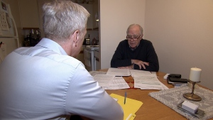 David Abbott shows Ross McLaughlin his medical bills following his heart attack in Britain. (CTV)