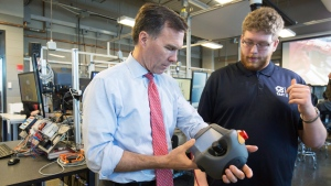 Minister of Finance Bill Morneau (L) puts on a robot controller at the robotics lab with student Spencer Pelzer while touring the Southern Alberta Institute of Techonology in Calgary, Alta., Monday, March 27, 2017.(THE CANADIAN PRESS/Todd Korol)