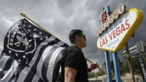 Matt Gutierrez carries a Raiders flag by a sign welcoming visitors to Las Vegas in Las Vegas on Monday, March 27, 2017. (AP / John Locher)