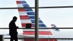 In this Jan. 25, 2016, file photo, a passenger talks on the phone as American Airlines jets sit parked at their gates at Washington's Ronald Reagan National Airport. (AP / Susan Walsh, File)