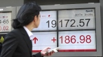 A woman looks at an electronic stock board showing Japan's Nikkei 225 index at a securities firm in Tokyo, Tuesday, March 28, 2017. (AP / Eugene Hoshiko)