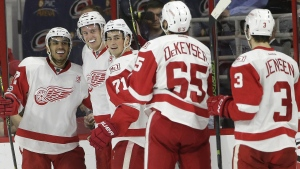 Detroit Red Wings' Anthony Mantha, second from left, is congratulated by Andreas Athanasiou, left, Dylan Larkin (71) Danny DeKeyser (65) and Nick Jensen (3) following Mantha's goal against the Carolina Hurricanes during the second period of an NHL hockey game in Raleigh, N.C., Monday, March 27, 2017. (AP / Gerry Broome)