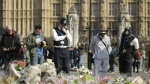 Police officers and members of the public look at the floral tributes to the victims of the Westminster attack placed outside the Palace of Westminster, London, Monday March 27, 2017. (AP / Matt Dunham)