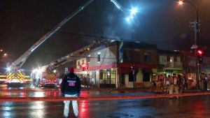 A police officer watches as firefighters extinguish a criminal fire at Chez Mon Copain on Hochelaga St. in Montreal