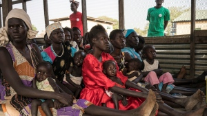 In this photo taken Monday, March 13, 2017, Iman Diing, 20, center, holds her 13-month-old baby daughter Alakaii at a UNICEF-supported outpatient therapeutic program for the malnourished, near Aweil, in South Sudan. (Mackenzie Knowles-Coursin/UNICEF via AP)