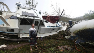 Bradley Mitchell inspects the damage to his uncle's boat after it smashed against the bank at Shute Harbour, Airlie Beach, Australia on Wednesday, March 29, 2017. (Dan Peled / AAP Image)